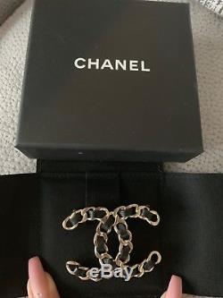 Chanel large brooch worn two times. Beautiful piece with black leather